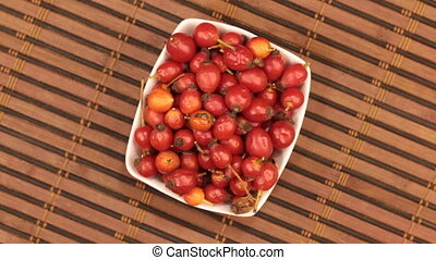 Rotating a dish with rosehips standing on a bamboo mat. View...