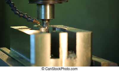 Rotating a drill a vertical drill press handles metal piece with a coolant drop by drop.