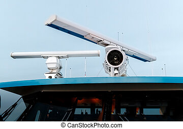 Rotating antenna of marine radar and searchlight on top of the ship.