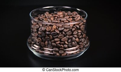 Rotating coffee beans in a glass vessel on a black background.