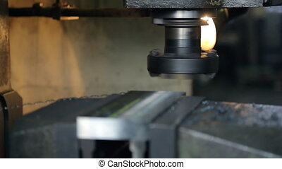 Rotating cutter lined metal part, which is clamped in a vise. Round head with incisors is stopped after operation produced metal parts. Smooth surface formed as a result of the grinding layer with blanks. Turner working gloves using short panicles shakes a bunch of shavings from the surface of the ...