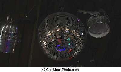 Rotating disco mirror ball in dark indoors