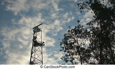 Rotating dish radar on telecommunication tower blue sky in...