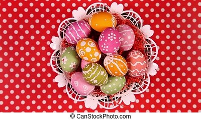 Rotating Easter eggs in basket, the red tablecloth as...