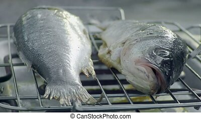 rotating fish on electric grill outdoor by hand and fork