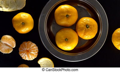 Rotating frash tangerines on black background