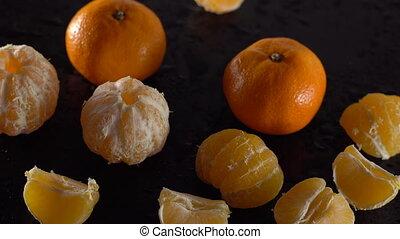 Rotating frash tangerines on black background
