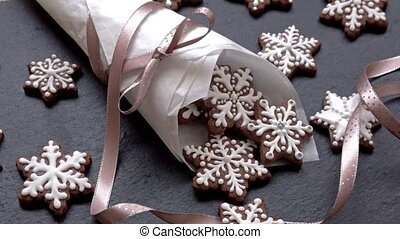 side view of rotating gingerbread cookies (snowflakes) in a paper cone on slate table