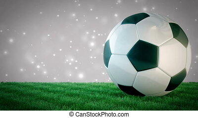 Rotating glossy soccer ball on grass field with bokeh...