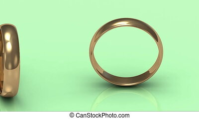 Rotating gold wedding rings on a green background
