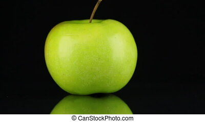 Rotating green apple and its reflection on a black background.