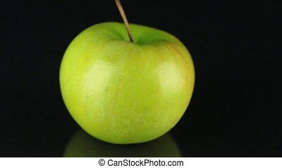 Rotating green apple on a black background. Fruit. Close-up