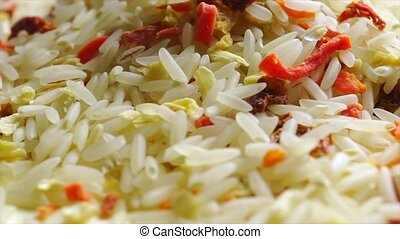 Rotating heap of uncooked rice and vegetables