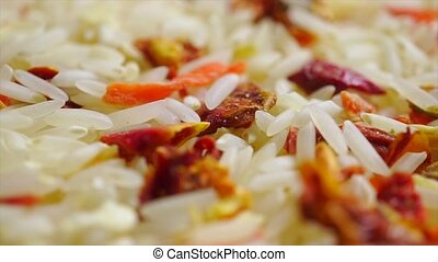 Rotating heap of uncooked rice and vegetables. Macro video...