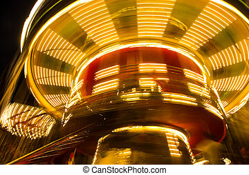 rotating lighted children's merry-go-round at night. Blurred...