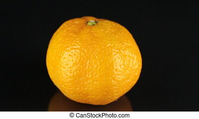 Rotating mandarin on a black background. Citrus.