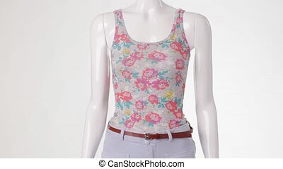 Rotating mannequin in floral top.