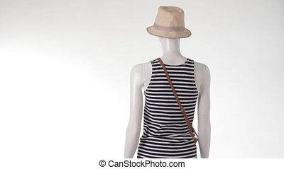 Rotating mannequin in striped top.
