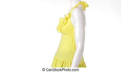 Rotating mannequin in yellow top. Backless yellow top with folds. Young lady's thin summer garment. Light clothing sold at discount.