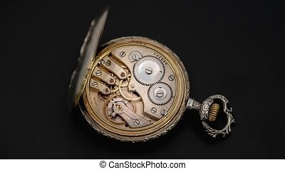Rotating mechanism of the gears of an antique pocket watch. Close up. Time lapse . Back background