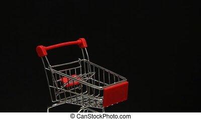 Rotating miniature metal empty shopping cart on black ...