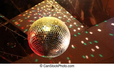 rotating mirror disco ball in night club, reflection of ...