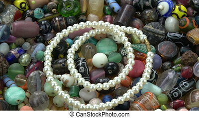 Rotating new luxury pearls necklace on old indian beads background