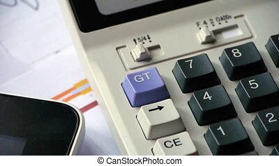 rotating of calculator & tablet pc with business graph chart on table.