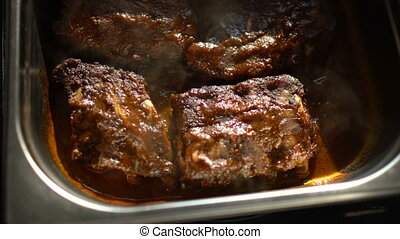 Rotating of hot meat dishes with pork ribs with gravy...
