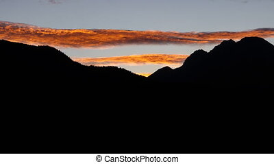 Rotating orange long cloud time lapse over black mountain...