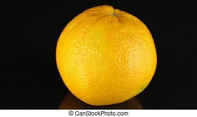 Rotating orange on a black background. Citrus. Close-up