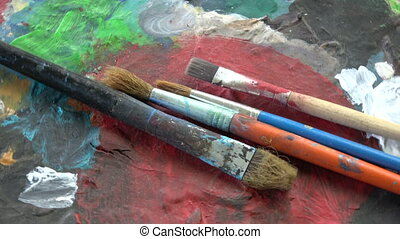 Rotating painter artist old palette with paintbrushes -...