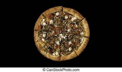 Rotating pizza with smoked sausage and olives on a black...