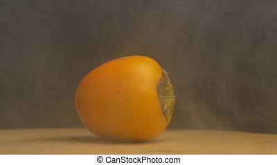 Rotating ripe persimmon from which blows freshness and...