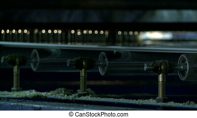 Rotating rollers on gluing machine, close-up