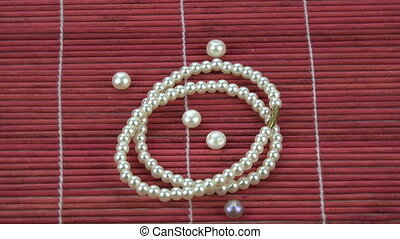 Rotating small String of pearls on red bamboo mat background