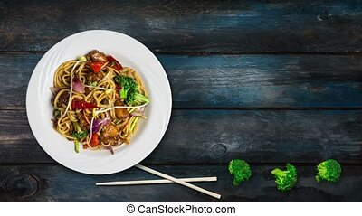 Rotating udon stir fry noodles with meat or chicken and vegetables. Decorated with fresh broccoli and chopsticks in a white plate on wooden background. Top view with the copy space for your text