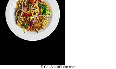 Rotating udon stir fry noodles with meat or chicken and vegetables. In a white plate isolated on ablack background. Square layout for social networks, copy space for your text