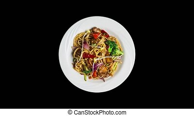 Rotating udon stir fry noodles with meat or chicken and vegetables isolated on ablack background. Top view