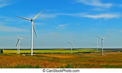 Scenic view of rotating wind turbines on field against blue sky