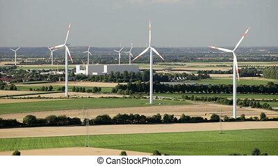Rotating wind turbines - Flat west German landscape near...