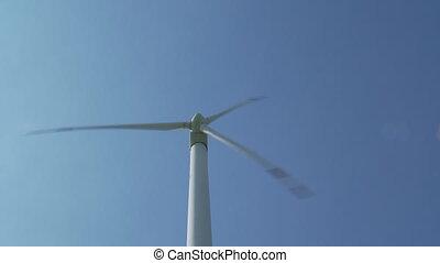 rotating windmill at blue sky