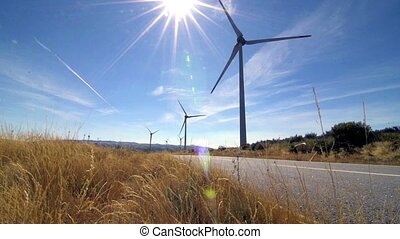 Rotating windmills and paved road. Alternative renewable energy generation.