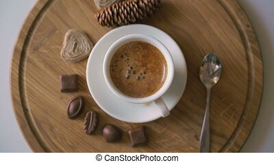 Rotating wooden background with coffee, candies and biscuit in 4K