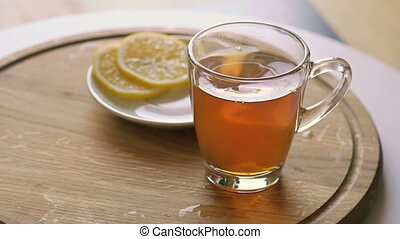 Rotating wooden background with tea and slices of lemon