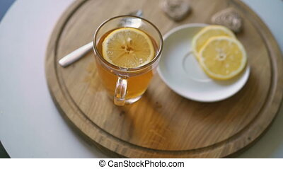 Rotating wooden background with tea, slices of lemon and biscuit