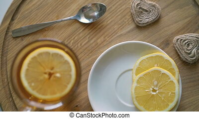 Rotating wooden background with tea, slices of lemon and biscuit in 4K