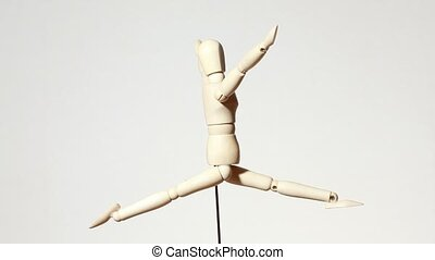 rotating wooden figure of jumping man with raised hands