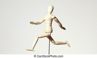 rotating wooden figure of running man on white background