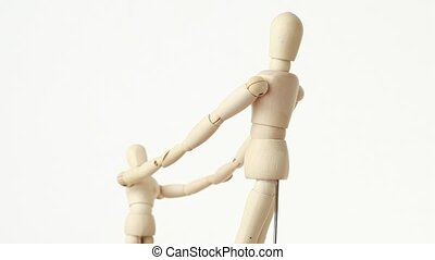 wooden figures of parent and his child have joined hands -...